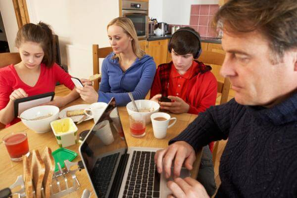 Teenage Family Using Gadgets Whilst Eating Breakfast