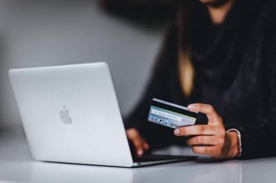 Woman with a laptop holding a credit card